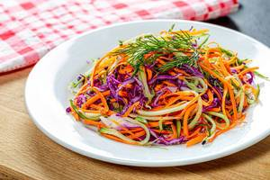 Fresh salad with carrots, cucumber and purple cabbage on a white plate (Flip 2019)