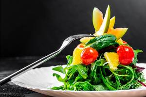Fresh salad with herbs, tomatoes, avocado and orange on a plate with a fork