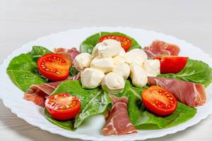 Fresh salad with jamon, mozzarella, tomatoes and Romaine lettuce