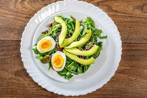 Fresh salad with lettuce, boiled eggs and avocado. Top view