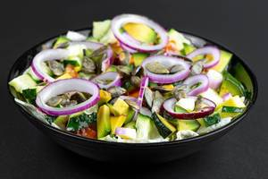 Fresh salad with sliced vegetables, purple onion rings and pumpkin seeds