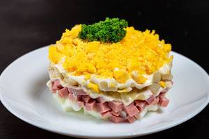 Fresh salad with vegetables, ham and sauce on black background (Flip 2019)