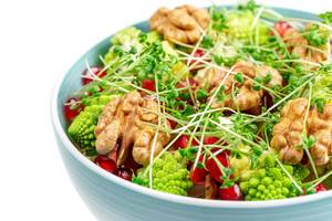 Fresh salad with walnuts, pomegranate and watercress, close-up