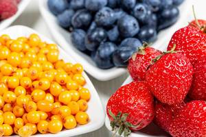 Fresh sea buckthorn berries, blueberries and strawberries closeup