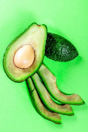 Fresh Sliced avocado on green background