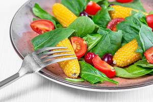 Fresh spinach, tomato slices, dogwood berries and corn. The concept of healthy food