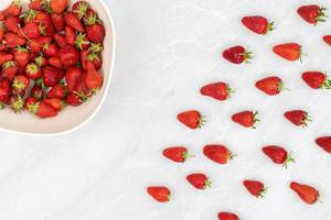 Fresh strawberries arranged on the table with strawberries in the bowl