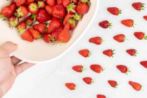 Fresh strawberries with blurred strawberries in the bowl