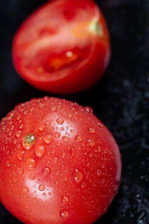 Fresh tomatoes with water drops on black background
