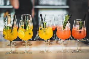 Fresh Tropical Summer Cocktails displayed in a Row on a Bar Table