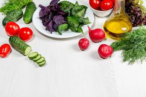 Fresh vegetables and herbs with olive oil. The concept of ingredients for cooking healthy food