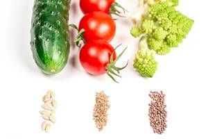 Fresh vegetables and their seeds on a white background