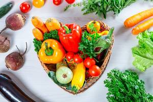 Fresh vegetables in the basket and around it on a white wooden background. Top view (Flip 2019)