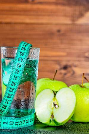 Fresh washed apple, water drops on a glass and a measuring tape