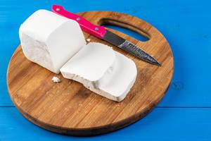 Fresh White Cheese on the round wooden board (Flip 2019)