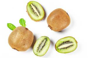 Fresh whole and slices of kiwi on a white background, top view