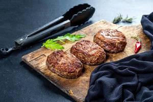 Freshly grilled burger meat on black background (Flip 2019)