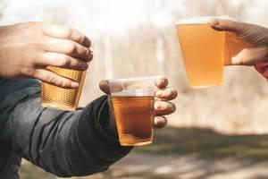 Freunde mit Bier in der Hand vor einem verschwommenen Natur-Hintergrund