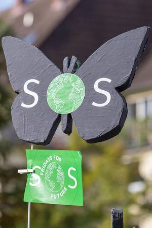 "Fridays for Future ""SOS"" Butterfly with planet earth - protest sign at the climate strike march in Cologne, Germany"