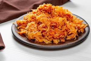 Fried cabbage in a brown plate on the table