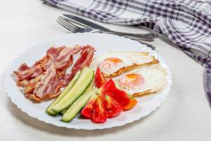 Fried eggs, bacon and pieces of fresh tomatoes and cucumbers. The concept of Breakfast