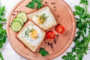 Fried eggs in toast bread with spices, vegetables and herbs