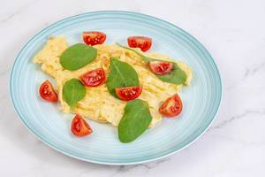 Fried Eggs with Baby Spinach and Cherry Tomato on the plate