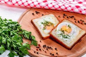 Fried eggs with toast bread on wooden kitchen Board
