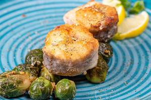 Fried fish with Brussels sprouts and spices closeup (Flip 2019)