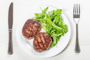 Fried meat patties and arugula on a white plate with a knife and fork (Flip 2019)