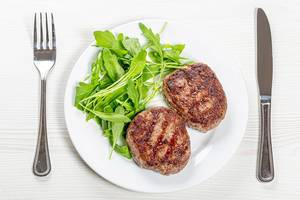 Fried meat patties and arugula on a white plate with a knife and fork