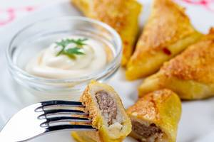 Fried pancakes with meat filling and white sauce