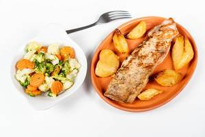 Fried Pork Steak with Potatoes and Vegetable Salad isolated on a clay plate