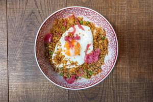 Fried Sunrice in the coa Wok & Bowls restaurant in Cologne: fried rice with peas, carrots, onions, chili, ginger, garlic and fried egg on the top