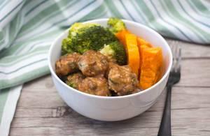 Frikadellen mit Soße, Broccoli und Kürbis in einer Schüssel vor einem Küchentuch