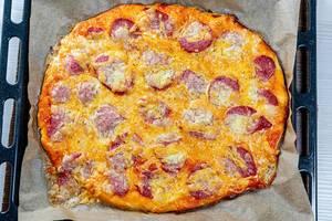 Frisch gebackene hausgemachte Pizza mit Wurst und Käse auf einem schwarzen Backblech