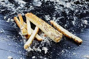 Frisch gebackene Käsestangen mit Kümmelsamen auf schwarzem Hintergrund