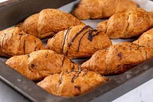 Frisch gebackene Schoko-Croissants auf einem Backblech
