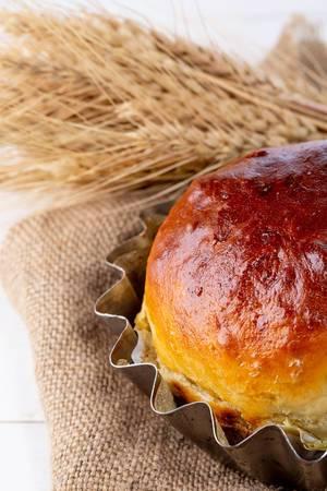 Frisch gebackenes Brot mit Weizenähren, auf einem Leinentuch, in der Küche