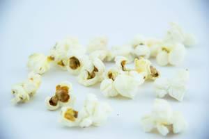 Frisch gebackenes Popcorn vor weißem Hintergrund