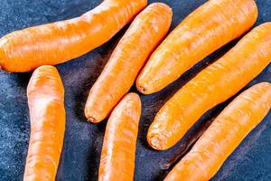 Frisch geerntete, satt orange Karotten mit Schale vor dunklem Hintergrund