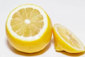 Frisch zugeschnittene, saure Zitrone mit Schale vor weißem Hintergrund