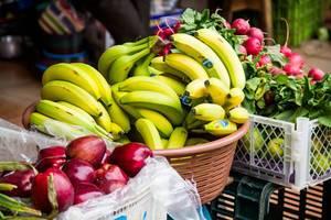 Frische Äpfel, Bananen und Radischen auf dem Markt
