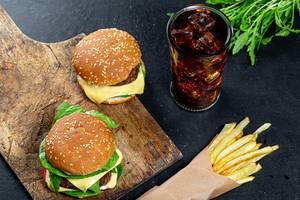 Frische Burger, eisgekühlte Cola und verpackte Pommes, auf einem dunkeln Küchentisch