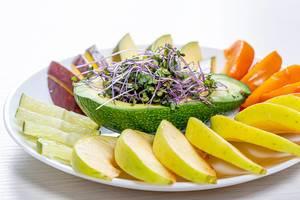 Frische Früchte geschnitten auf einem weißen Teller mit Avocado und mikrogrünem Kohl