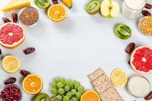 Frische Früchte, Getreide, Milchpulver und Brot auf einem weißen Holzhintergrund mit Freiraum in der Mitte