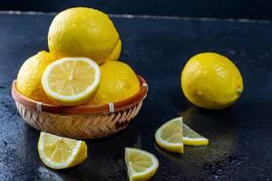 Frische ganze und geschnittene gelbe Zitronen auf einer dunklen Tabelle