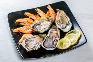 Frische große Austern neben Zitronenscheiben und Garnelen, auf einem schwarzen Teller