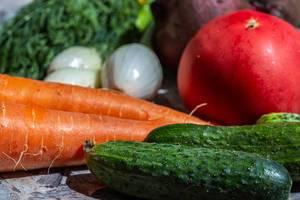 Frische Gurken, Möhren, Zwiebeln, Tomaten und Rote Bete liegen für ein gesundes Essen auf der Küchenarbeitsfläche bereit