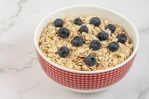 Frische Haferflocken, pur, mit Blaubeeren, in einer Müslischüssel im Landhausstil, für ein leckeres Frühstück